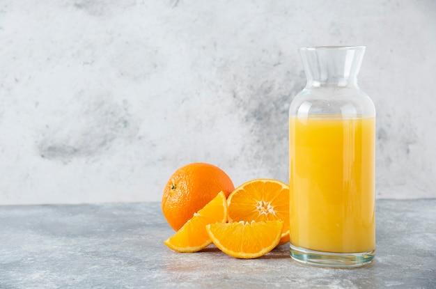 Brocca di vetro di succo con fetta di frutta arancione.