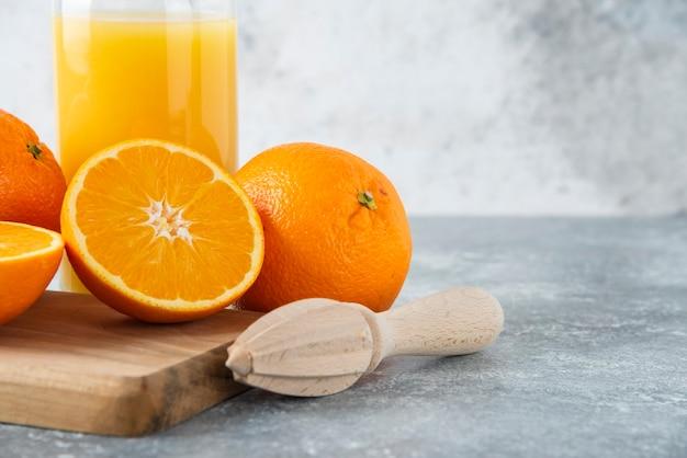 Brocca di vetro di succo con frutta arancione a fette su una tavola di legno.