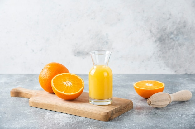 Glass pitcher of juice with sliced orange fruit on a wooden board .
