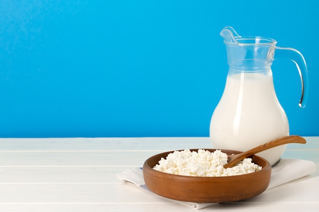 Glass pitcher of milk and bowl of cottage cheese on wooden table