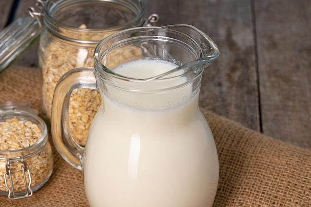 Glass pitcher of milk and oat flakes on wooden table