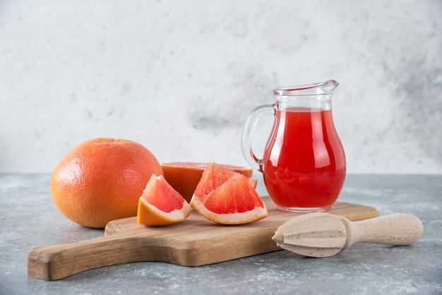 フルーツのスライスと新鮮なグレープフルーツジュースのガラスピッチャー。