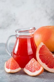 Стеклянный кувшин свежего грейпфрутового сока с кусочками фруктов.