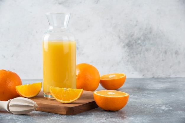 Стеклянный кувшин сока со свежими апельсиновыми фруктами на деревянной доске.