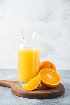 Стеклянный кувшин сока с ломтиком апельсина.