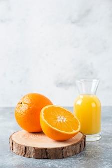 Стеклянный кувшин сока с ломтиками апельсина на деревянной доске.