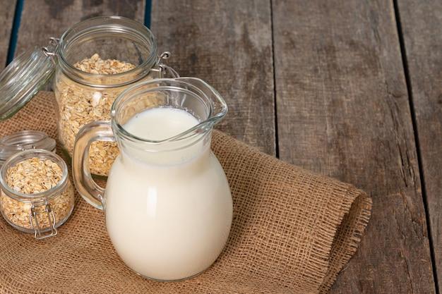 나무 테이블에 우유와 귀리 플레이크의 유리 투 수