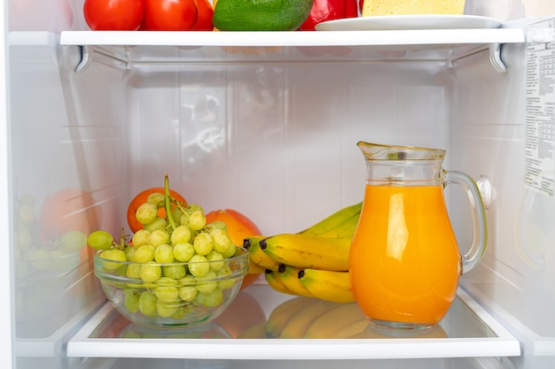 冷蔵庫の棚にオレンジジュースと果物のガラスピッチャーをクローズアップ