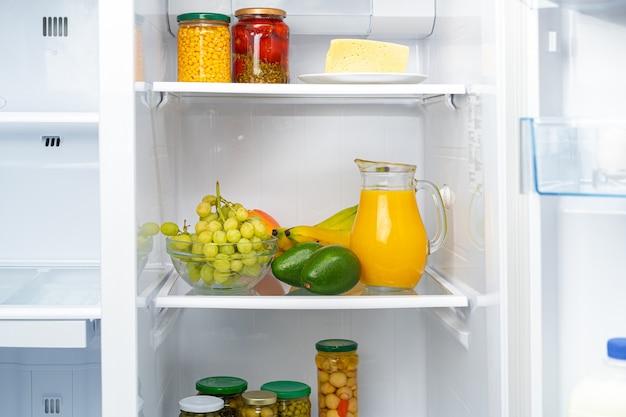 冷蔵庫の棚にオレンジジュースと果物のガラスピッチャー