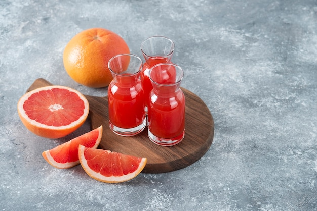 Glass pitchers of fresh grapefruit juice with slices of fruits placed on a wooden round board .
