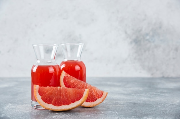 Glass pitchers of fresh grapefruit juice with slices of fruits .