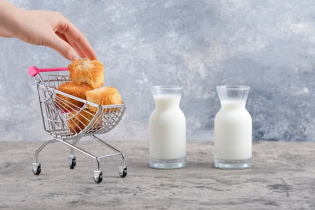 Glass pitchers of fresh milk with delicious cookies placed on a marble background.