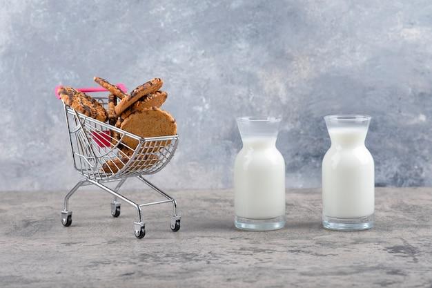 Brocche di vetro di latte fresco con deliziosi biscotti posti su un tavolo di marmo.