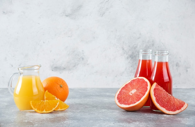 Glass pitchers of grapefruit juice with slices of orange fruits.