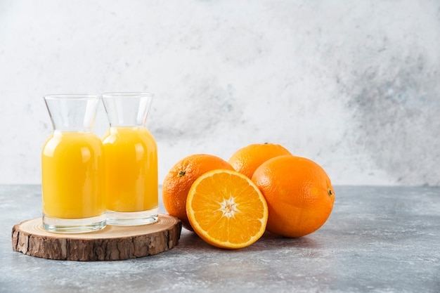 Glass pitchers of juice with slice of orange fruit .