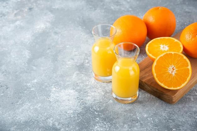 Brocche in vetro di succo con fettina di arancia.