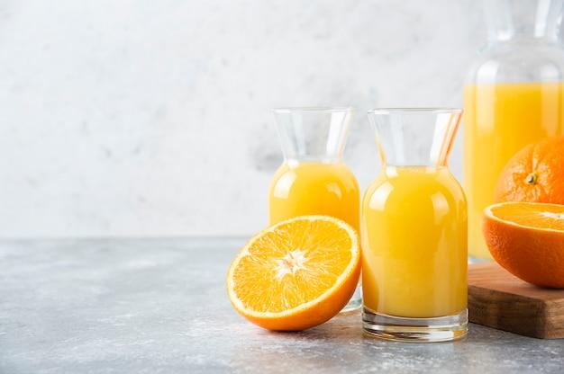 Glass pitchers of juice with slice of orange fruit .