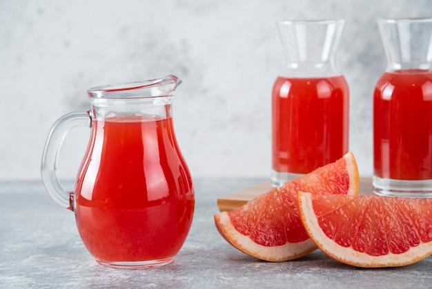 Стеклянные кувшины свежего грейпфрутового сока с кусочками фруктов.