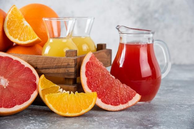 オレンジフルーツのスライスとグレープフルーツジュースのガラスピッチャー。