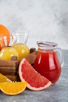 Стеклянные кувшины грейпфрутового сока с дольками апельсиновых плодов.