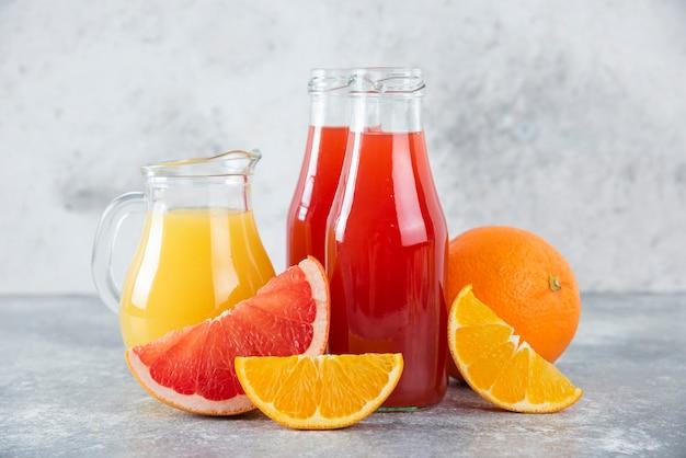 오렌지 과일 조각과 자몽 주스의 유리 투수.