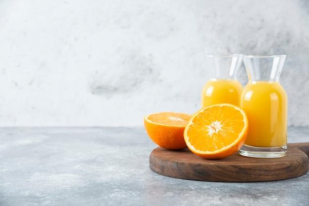Стеклянные кувшины сока с ломтиком апельсина.