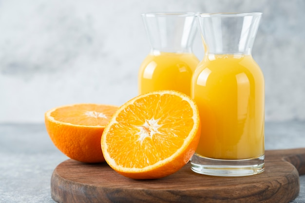 オレンジ色の果物のスライスとジュースのガラスピッチャー。