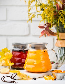 Glass pitchers with red tea and cape gooseberry tea