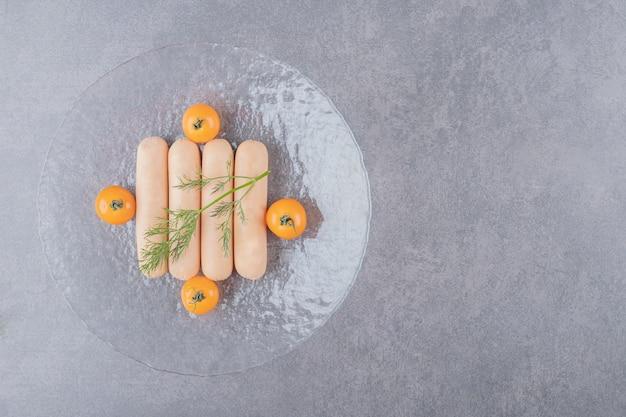 Un piatto di vetro di salsicce bollite con pomodorini gialli