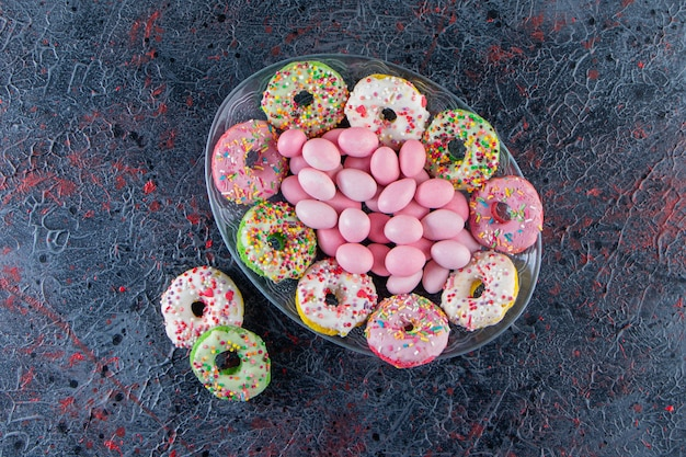 Glass plate of colorful delicious donuts and pink candies on dark surface.