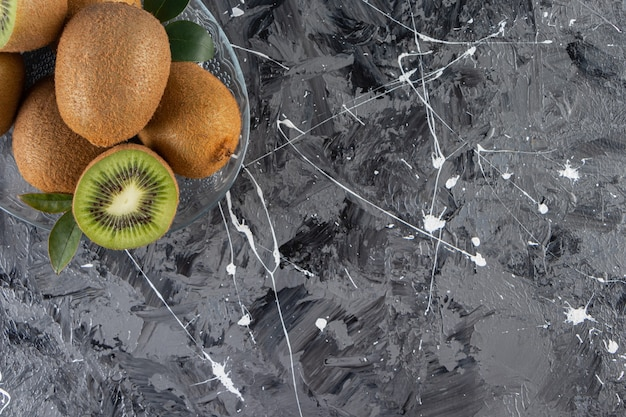 Glass plate of delicious kiwi fruits on marble surface