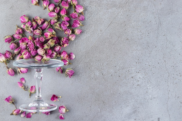 A glass plate full of dried rose flower buds placed on stone background.