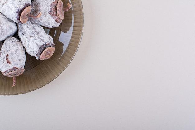 흰색 바탕에 말린 감으로 가득 찬 유리 접시. 고품질 사진
