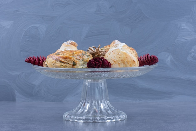 A glass plate full of pastries and christmas pinecones