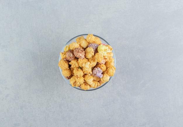 Un piatto di vetro pieno di popcorn con caramello.