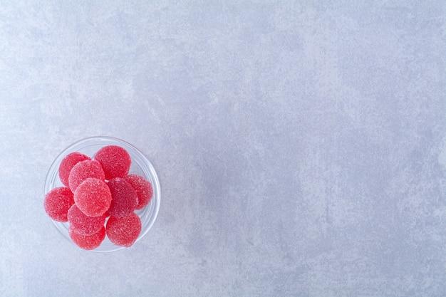 Un piatto di vetro pieno di caramelle di gelatina di frutta zuccherata rossa su superficie grigia