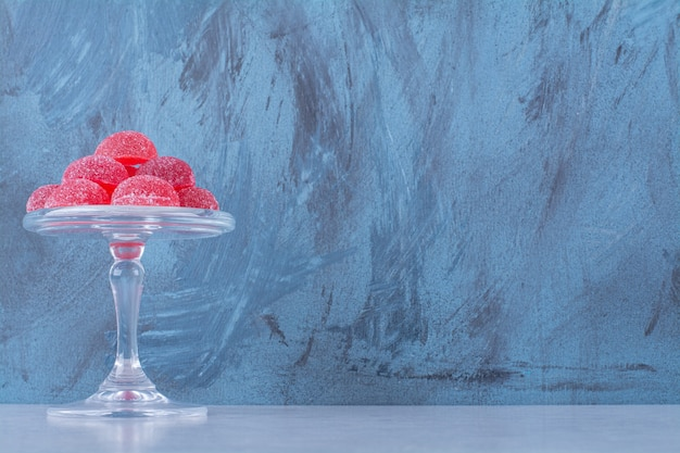 Una lastra di vetro piena di caramelle di gelatina di frutta zuccherata rossa sul tavolo grigio.