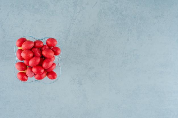 Un piatto di vetro pieno di dolci e deliziose caramelle rosse su una superficie bianca