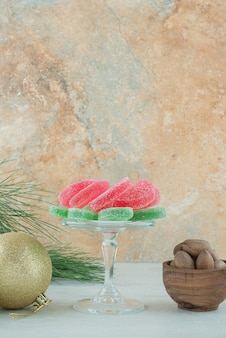A glass plate of marmalade and wooden bowl of nuts on marble background. high quality photo