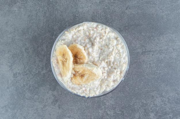 Un piatto di vetro di porridge di farina d'avena con fette di banana.