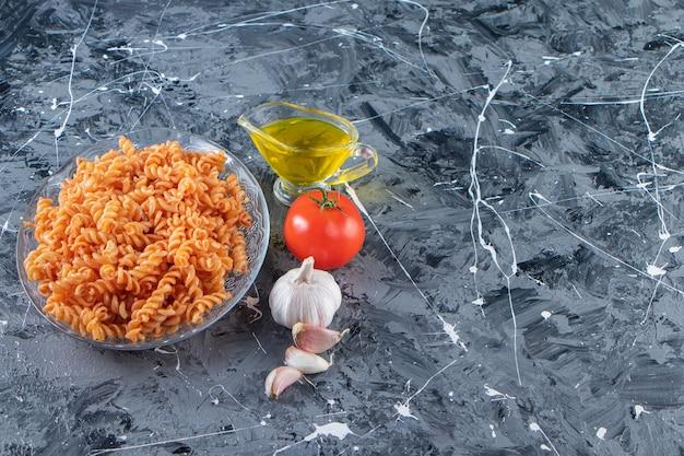 大理石の背景においしいフジッリパスタと野菜のガラス板。