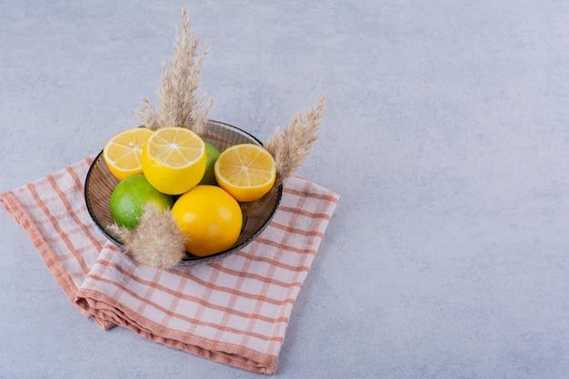 Стеклянная тарелка свежих сочных лимонов на каменном столе.