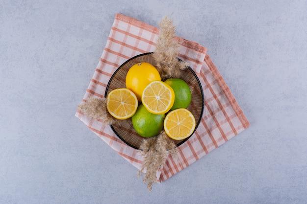 Стеклянная тарелка свежих сочных лимонов на камне.
