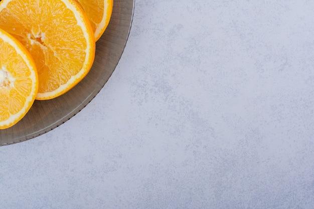 石の上の新鮮なオレンジスライスのガラス板。