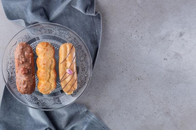돌 배경에 다양 한 채워진 된 eclairs의 유리 접시.