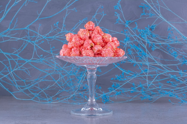 Glass plate of pink popcorn balls on stone surface