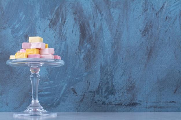 Un piatto di vetro di pasticceria dolce rosa e gialla pastila