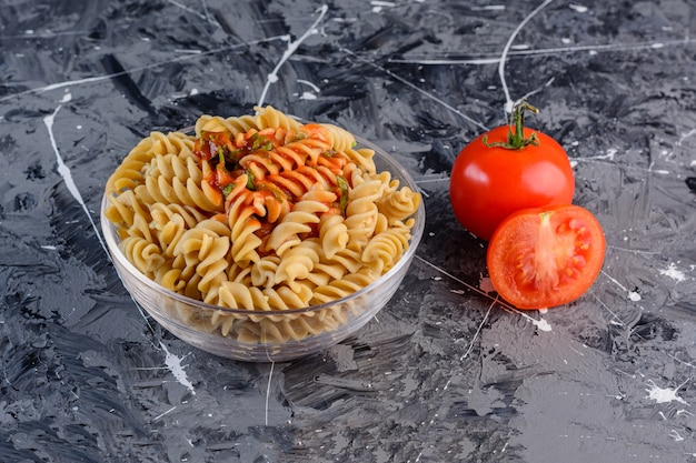 A glass plate of raw dry multi colored fusilli pasta with fresh red tomatoes