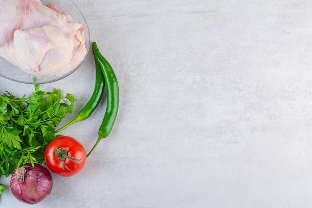 Lastra di vetro di pollo intero crudo con verdure fresche sulla superficie della pietra