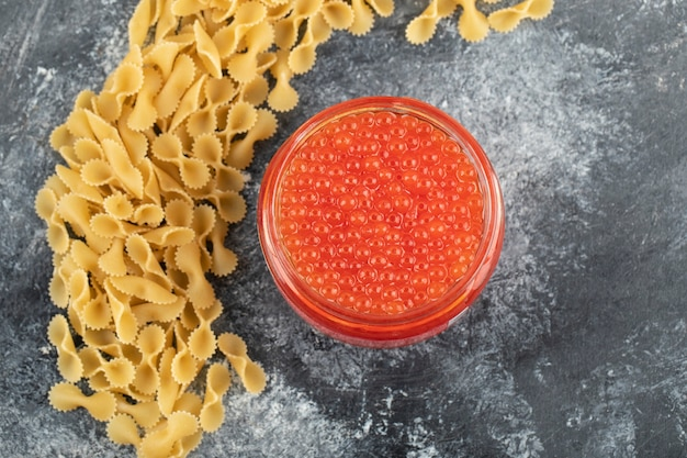 A glass plate of red sturgeon caviar with uncooked pasta .
